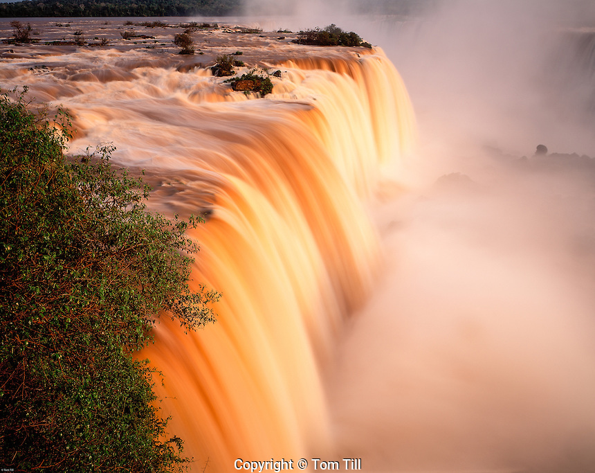 Sunset Light on Iguazu Falls, Iguazu Falls National Park, Brazil    Red colors from plant tannins in water    UNESCO World Heritage Site