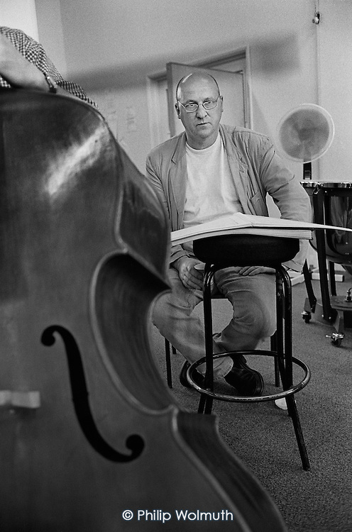 English composer and double-bassist Gavin Bryars. Orchestral rehearsal of his opera Doctor Ox's Experiment at the ENO's Islington rehearsal studios, London.