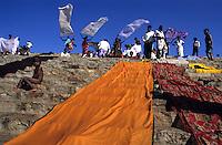 INDIA Karnataka, every year a festival takes place around the Yellamma temple in Saundatti and attracts thousand of pilgrims from villages, here is also practizised the Devadasi cult, where young girls are secretly dedicated to the hindu goddess Yellamma, most of the girls end in prostitution, pilgrim dry sari after holy bath in pond Jogal Bhavi  / INDIEN Karnataka, jedes Jahr findet in Saundatti das Tempelfest zu Ehren der Goettin Yellamma statt, das Tausende Pilger aus den umliegenden Doerfern anzieht, hier wird der Devadasi Kult praktiziert, heimlich werden junge Maedchen der Hindu Goettin Yellamma geweiht, die Maedchen enden spaeter meistens in der Prostitution, Pilger trocknen Saris nach Bad im heiligen Brunnen Jogal Bhavi
