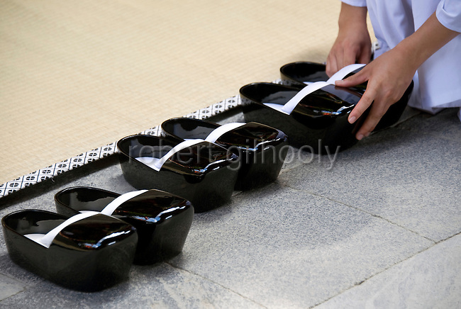 A young shrine attendant arranges the clogs of shrine priests left at the entrance to the inner sanctuary of the main hall prior to a ritual on the second day of the 3-day Reitaisai festival at Tsurugaoka Hachimangu shrine in Kamakura, Japan on  15 Sept. 2012.  Photographer: Robert Gilhooly