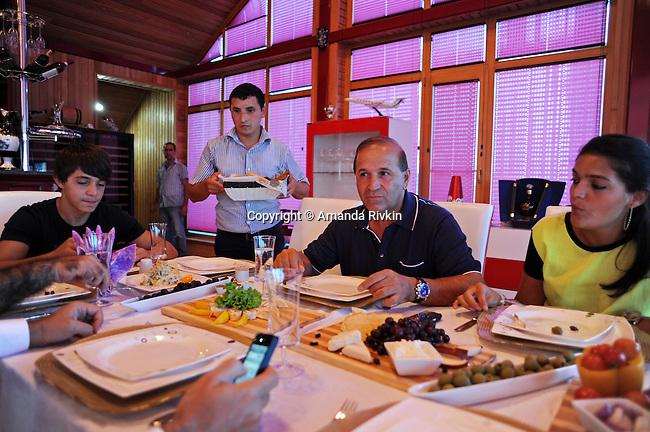 Ibrahim Ibrahimov (center) sits down for dinner with his son Hasan, 16, and daughter Ilkana Ibrahimova, 22, in his home between Sangachal and Sahil, Azerbaijan on August 16, 2012.