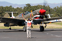 A P-40 Warhawk owned and flown by Tony Banta and based in Livermore, California is guided into its position on the ramp by a Flight Line Safety Officer during the 2007 Wings Over the Wine Country Airshow at the Charles. M Schulz Regional Airport in Santa Rosa California. The Wings Over the Wine Country Airshow is held annually during the month of August and sponsored by the Pacific Coast Air Museum. Photographed 08/07