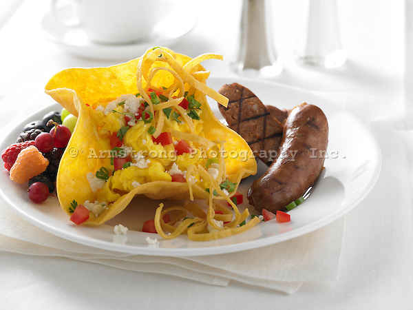 Tex-Mex breakfast of scrambled eggs in a taco shell, sausage, and fresh fruit