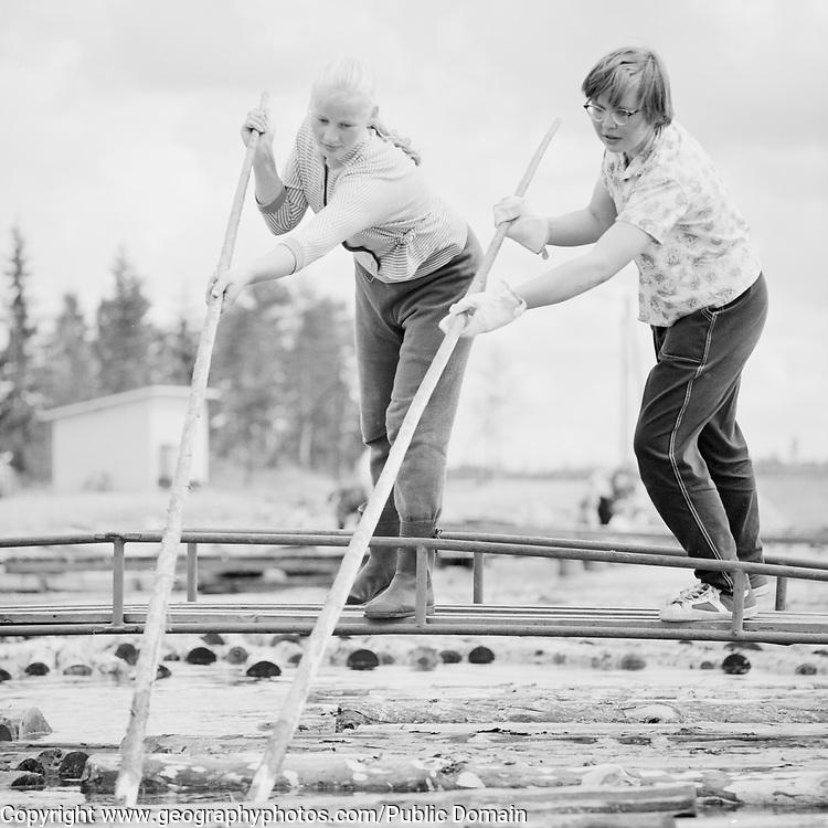 Two young women pushing logs in a river, Finland, 1959