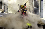 Smoke wraps around an East Hartford firefighter works to open up a section of roof on the 1st floor porch to vent the heat and fire during a 2 alarm fire on Phelps St in East Hartford Friday . A Jim Michaud pic 2/23/01