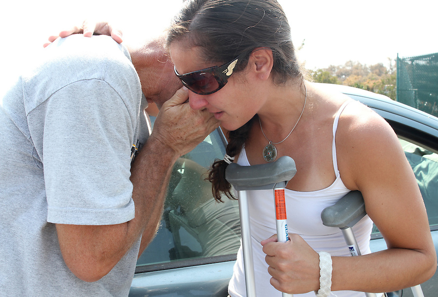 Heather Fleming consoles her boyfriend Jim Meyer after Meyer called his daughter to say he had survived Hurricane Irene and a house fire next to his Rodanthe, NC home.  The two were catching a ferry off of Hatteras Island to the mainland in Stumpy Point, NC, on Monday, Aug. 29, 2011. Photo by Ted Richardson