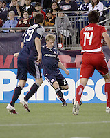 New England Revolution defender Seth Sinovic (27) crosses the ball to New England Revolution midfielder Marko Perovic (29) with FC Dallas defender George John(14) preparing to intercept.  The New England Revolution drew FC Dallas 1-1, at Gillette Stadium on May 1, 2010