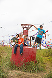 USA, Washington State, Long Beach Peninsula, International Kite Festival, kids play on top of an old weather buoy