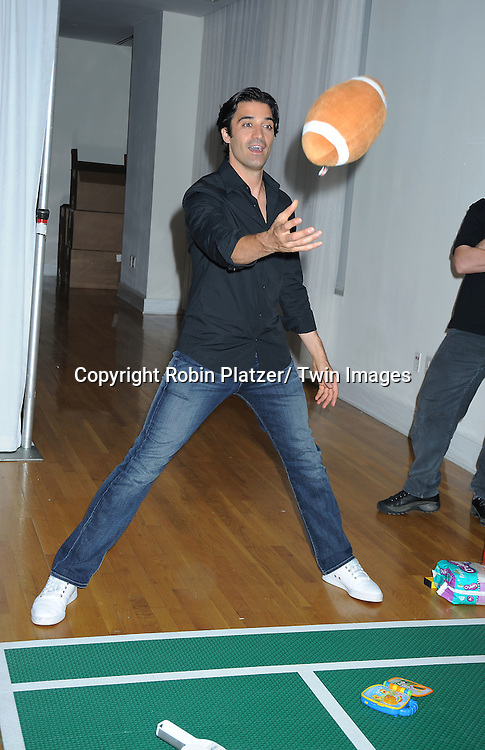 """Gilles Marini playing football at the kick-off of Father's Day week with  The Pampers with Dry Max Pays Homage to """"Dads on Diaper Duty""""  event on June 17, 2010 at The Metropolitan Pavilion in New York City."""