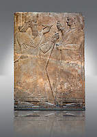 Assyrian relief sculpture panel  of King  Ashurnasirpal II demonstrating his perfect kingship by raising a ritual bowl whilst an attendant waves a whisk to maintain the king's purity.  From Nimrud, Iraq.  865-860 B.C North West Palace.  British Museum Assyrian  Archaeological exhibit.