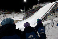 Official opening of Holmenkollen ski jump. Youngskijumpers watch the female ski jumper Anette Sagen perform the first official jump