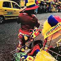 A Colombian woman sells football fan hats in national flag colors on the street in Cali, Colombia, 24 June 2014.