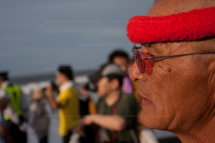 Portrait of a mikoshi supporter during the Hamaorisai Matsuri that takes place on Southern Beach in Chigasaki, near Tokyo, Kanagawa, Japan Monday July 18th 2011. The festivals marks the celebration of Marine Day and the rescuing of a divine image that was washed ashore in the area. Over thirty Mikoshi or portable shrines are carried through the night from surrounding shrines to arrive on the beach for sunrise. There they are blessed and then carried into the surf to purify them.