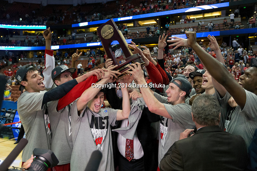 Wisconsin Badgers celebrate with the West Regional Trophy after the regional final NCAA college basketball tournament game against the Arizona Wildcats Saturday, March 29, 2014 in Anaheim, California. The Badgers won 64-63 (OT). (Photo by David Stluka)