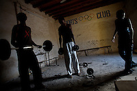 young somali refugees lift weights in the Kharaz refugee camp In  Yemen on Tuesday November the 27th 2007. THe camp, former military barracks, hosts 9000 somali refugees, most of which have become stable residents, completely dependent on humanitarian donations.  Somalis are allowed to work in Yemen, but due to the a 35% unemployment rate in the country, most of them remain jobless.///..Ever since the collapse of the Siad Barre regime in 1991 Somali men, women and children have been arriving at the port of Bosasso to buy passage in small open fishing boats to Yemen, where they are given automatic political asylum..The  boat trip, costing from 70 to 150 usd per person, can be often fatal due to the roughness of the sea, the overcrowded boats and the merciless of the smugglers..On the night of Nov 29 2007 a small fishing boat while trying to download it's load of refugees a few hundred meters from the Yemeni  shores of Meifa Haja, flipped over and was overwhelmed by the constant waves. of its 130 passengers, only 42 reached the UNHCR ( United Nations High Commissioner for Refugees )  refugee center in Meifa. 30 bodies where recovered the next day.  the rest are still unaccounted for.. UNHCR  estimates more than 80.000 somali refugees live  in the country residing mostly in shanty towns in Sana'a' and Aden.