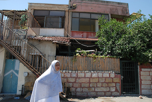 A palestinian family who has been expelled from their house is assisting the installation of a jewish settler family, protected by the army. There were 1967 refugees.