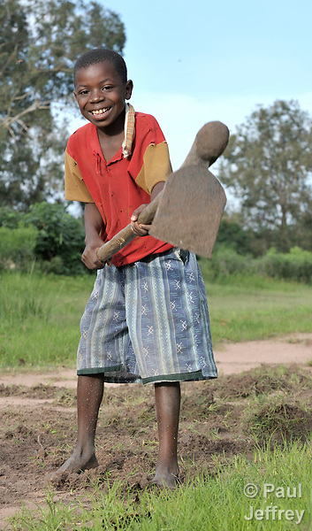A boy hoes his family's land in preparation for planting, at the edge of Kamina, in the Democratic Republic of the Congo.
