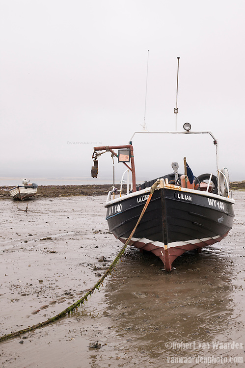 A boat rests on the mud flats of Holy Island in Scotland, the United Kingdom.
