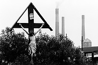 "Poland. Silesia. Bobrek. Jesus Christ on the wooden Holy Cross. "" Hutta Bobrek "" is the factory's name. Major polluted area due to old iron and steel works and heavy metals supended in the air. Bobrek is a small town, distant 20 km from Katowice. © 1991 Didier Ruef"
