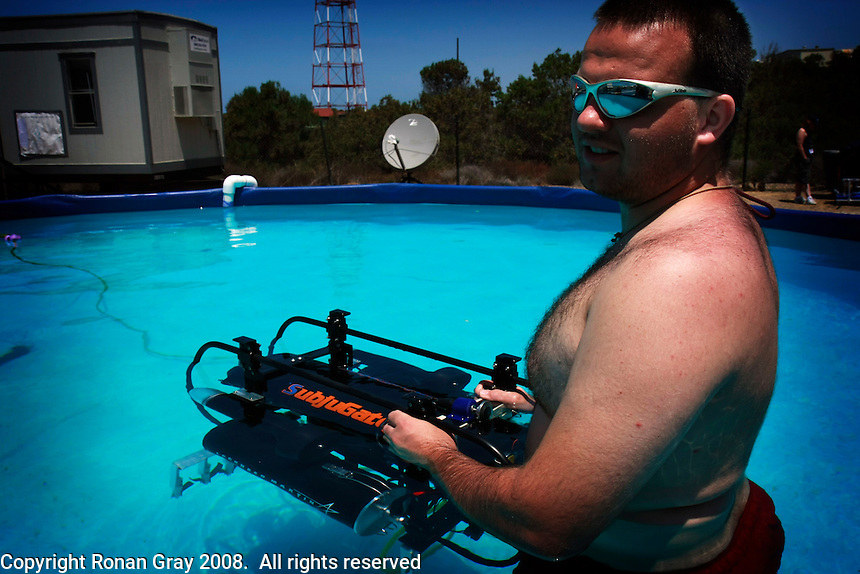 "TRANSEC Sonar Test Basin, Point Loma, San Diego, CA, USA. Friday, August 1 2008.  Tom Fenney of the Florida Institue of Technology holds his teams Autonomous Underwater Vehicle ""Subjugator"" in  a test pool next to the TRANSDEC pool at the site of the 2008 AUVSI underwater vehicle competition."