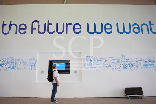 """A man looks up to read the conference theme, """"The Future We Want"""" on the wall of the Rio Centre venue.  United Nations Conference on Sustainable Development (Rio+20), Rio de Janeiro, Brazil. Photo © Sue Cunningham."""
