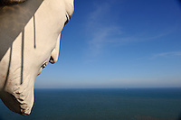 """Face of """"Christ of Vung Tau"""" overlooking the South China Sea. """"Christ of Vung Tau"""" is a statue of Jesus standing on Nui Nho (Tao Phung, or Little Mountain), in Vung Tau. Built between 1974 and 1993, it is 32 metres (105 ft) high, standing on a 4 metre (13 ft) high platform, for a 36 metre (118 ft) total monument height, with two outstretched arms spanning 18.3 metres (60 ft). There is a 133-step staircase inside the statue leading to observation points on both shoulders. Vung Tau, Vietnam"""