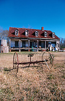 The exterior of the Woodlawn plantation house with an old combine in the forground. Venice, Louisiana.