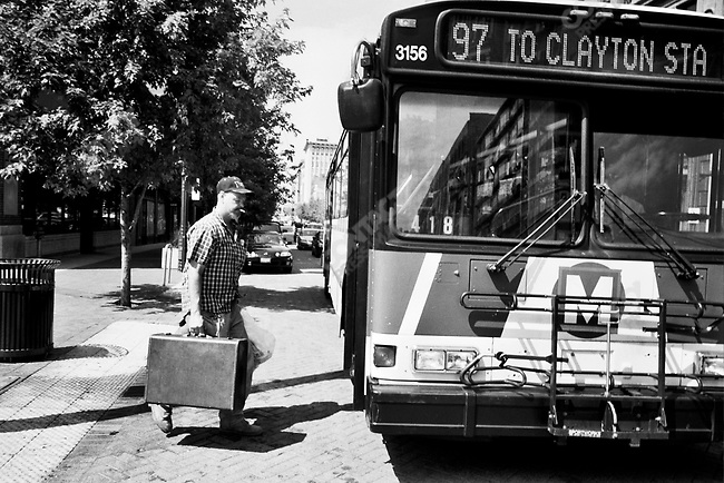 A passenger steps on to a bus heading for Clayton Station in St. Louis, Missouri, USA, September 2007