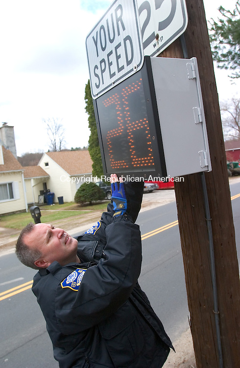 WATERBURY, CT. 24 March 2010-032410SV01-- Police officer Greg LaFountain installs a speed indicator on Perkins Avenue in Waterbury Wednesday. The department received three of these devices through a grant. The device lets drivers know what their actual speed is while traveling the road. The speed indicator also records your speed on a microchip letting police know how fast drivers are traveling the road. LaFountain is part of the community policing program.<br /> Steven Valenti Republican-American