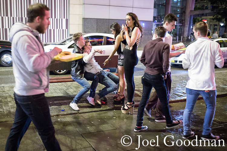 © Joel Goodman - 07973 332324 . No syndication permitted . 01/01/2014 . Manchester , UK . A collapsing man is held up by another man . Revellers see in the New Year in Manchester today (January 1st 2014) as police report that officers are at full stretch responding to calls . Photo credit : Joel Goodman