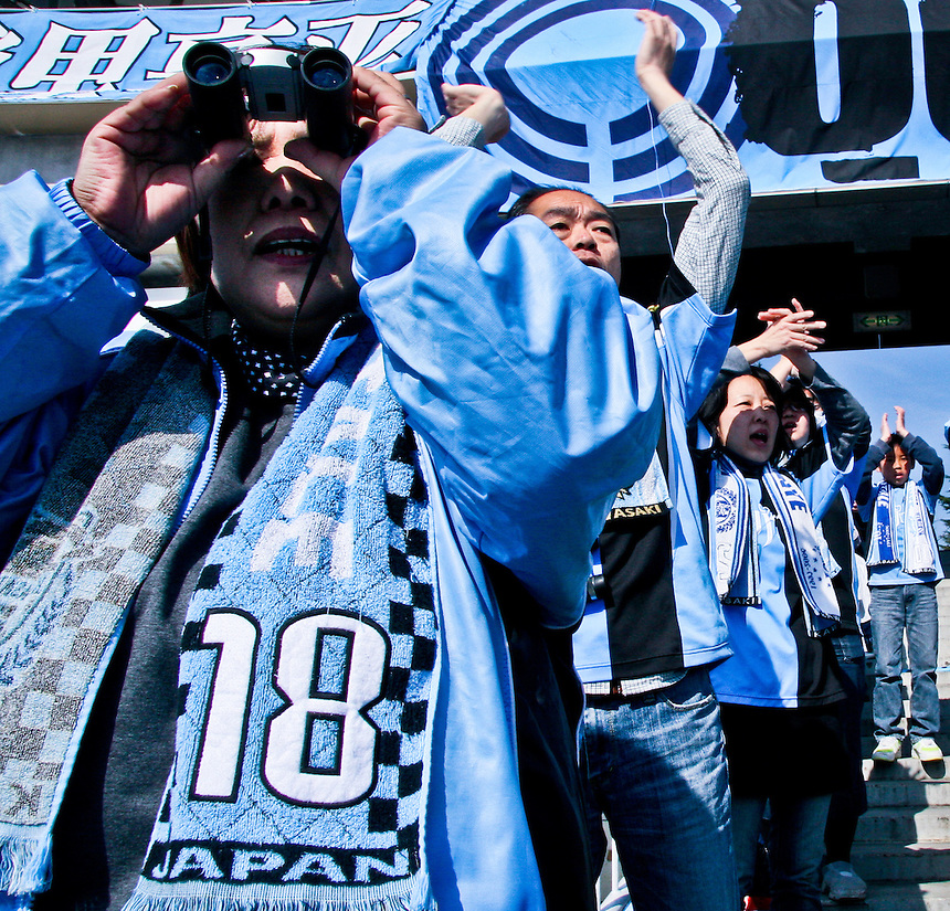 Kawasaki FRontale soccer fans dressed in team colours cheer them on.
