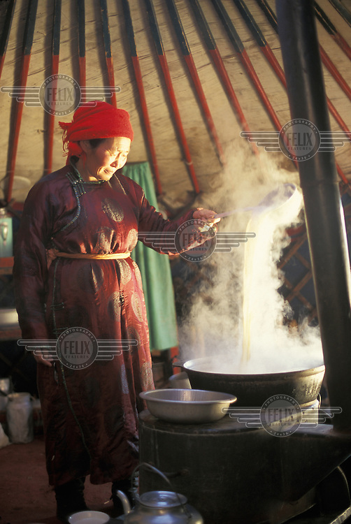 © Giacomo Pirozzi / Panos Pictures..Mongolia...Woman making tea in her gur. The tea is made with butter and horse's milk.