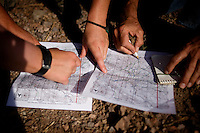 No More Deaths volunteers look at trail maps to decide where a water drop patrol will take place outside Arivaca, Arizona from July 21, 2009. Members of No More Deaths have spent years walking the trails in the Arivaca region and have created an elaborate system of water drops designed not only to meet, but also to help track migrant crossing patterns...PHOTOS/ MATT NAGER