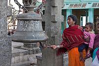 Kathmandu, Nepal.  Nepali Worshipper with Child Rings a Bell at Swayambhunath Temple.  Bells drive evil spirits away.