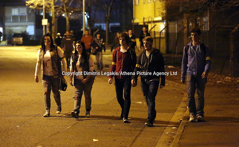 Pictured: Players walk around Cardiff. Saturday 29 March 2014<br /> Re: Cardiff thrill-seekers were chased around the city last night by a horde of terrifying zombies as part of virtual apocalypse game 2.8 Hours Later.<br /> Starting in Grangetown, groups of zombie-enthusiasts walked, jogged, hid and run around a quarantined area of the city, which included Cardiff City Stadium and Ninian Park Primary School, to escape a deadly mass of infected undead.<br /> But it wasn't just zombies threatening to disturb the peace of the city – aggressive police and surveillance squads forcing people to stand up against walls and avoid their harmless friends for fear of spreading infection wreaked havoc in the quarantine.
