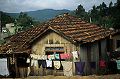 Ilha de Sta Catarina, Brazil. Small rustic timber house with tiled roof and washing hanging outside the window.