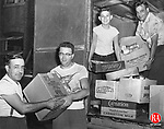 Food for disaster struck families is unloaded at the I. Dibner & Brothers Inc. dress manufacturing plant on Cherry Street in Waterbury. This supply of food was donated by the International Ladies Garment Workers Union of New Have nand was hauled to Waterbury by a Dibner truck. In the photo, from left, are Jack Angelillo, Mike Primack, and Henry Angelillo.