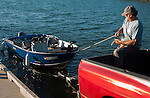 Man guides fishing boat onto trailer at the lake boat ramp