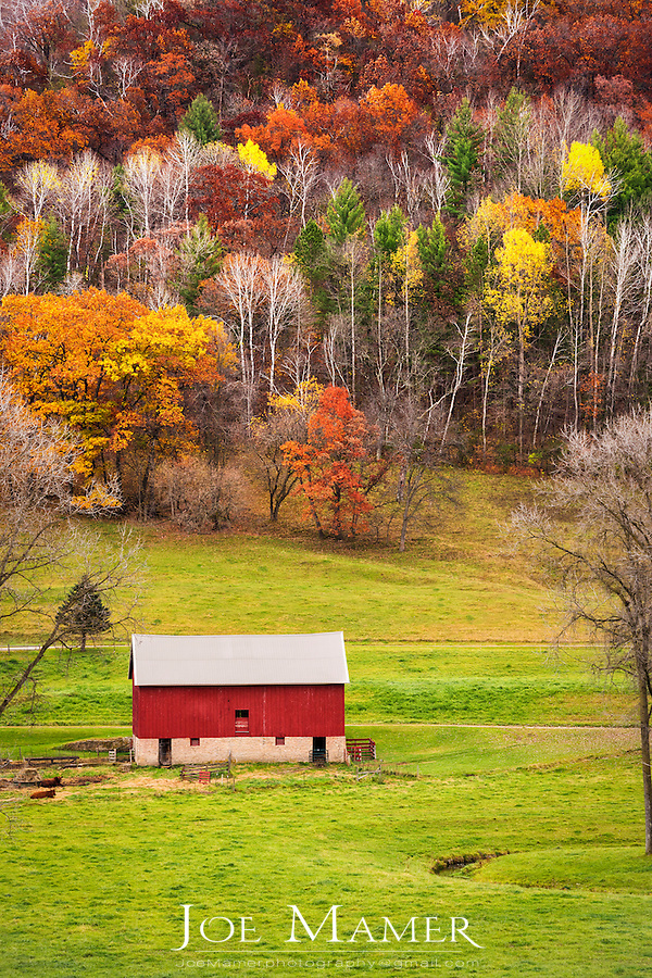 Red barn in valley with colorful autumn trees.