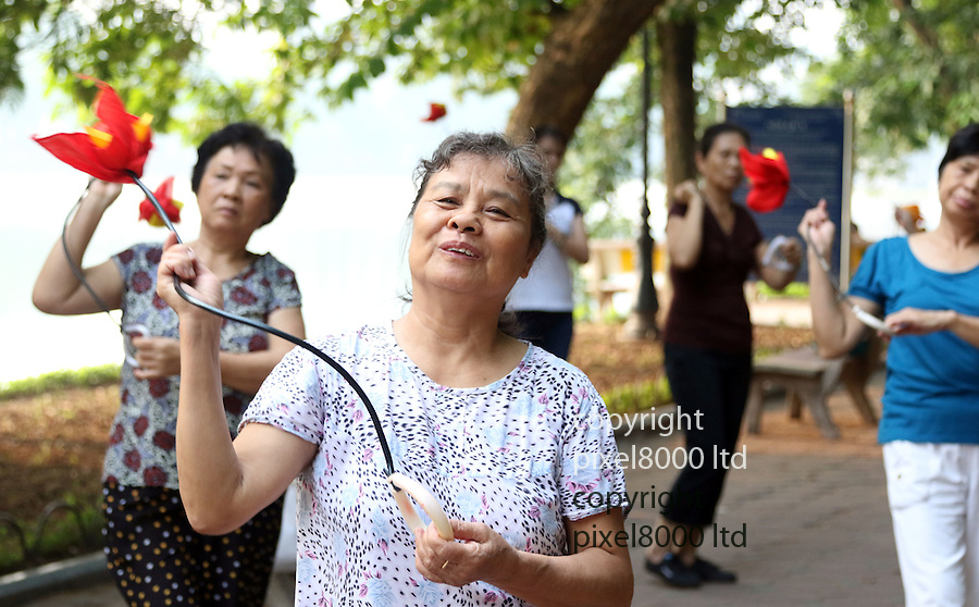 "Pic shows: Elderly people early morning workouts in Hanoi, Vietnam. <br /> <br /> Flower dancing<br /> <br /> Every morning starting as early as 5.a.m  hundreds of OAPS flock to the Hoan Kiem  (Lake of the Restored Sword) Lake in the centre of town.<br /> <br /> Unlike their Western counterparts who might be having breakfast and watchingTV they come to keep fit in various ways.<br /> <br /> Exercising daily into their 80's and even 90's the North Vietnamese partake in yoga, tai chi, dancing, badminton, weights and stretching exercises beside the picturesque<br /> lake.<br /> <br /> 89 year old ""Mr Kim"" sporting dark glasses and a traditional North Vietnamese pith helmet said ""I was a soldier in the war. I am used to keeping myself fit. <br /> <br /> ""I come very early most mornings. It is too hot to sleep anyway at this time of the year. I can't afford air conditioning.<br /> <br /> ""My back hurts a bit so I take it easy. I just do a few yoga stretching exercises on this bench to keep myself supple.<br /> <br /> ""It's also a lovely place to meet friends and share a cup of green tea and maybe packet of biscuits.""<br /> <br /> <br /> <br /> <br /> <br /> <br /> Pic by Gavin Rodgers/Pixel 8000 Ltd"