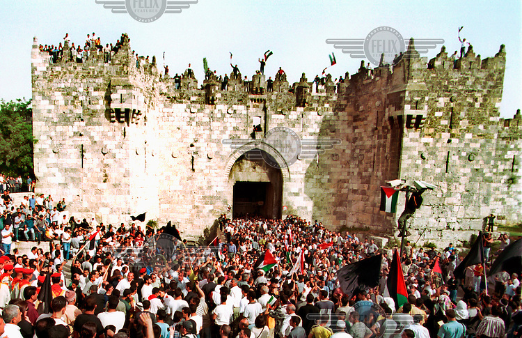 Palestinians entering the Damascus Gate in the Old City during the funeral of Faisal Hussaini.  For once the Israeli authorities placed no restrictions on Palestinians entering Jerusalem from the West Bank..Faisal Hussaini was one of the main Palestinian leaders and the representitive of the Palestinian Authority in Jerusalem where the Orient House acted as his base.  Hussaini died from a heart attack in Kuwait on May 31st. His funeral procession started in the Orient House, and ended in his burrial place in Haram-El-Sharif (Temple Mount).