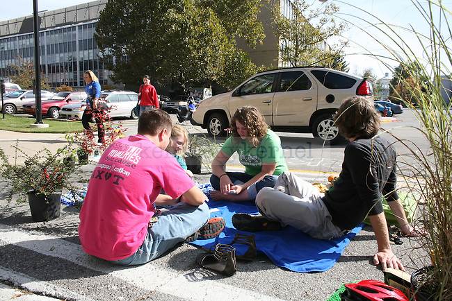 The UK Greenthumb club sits in parking spaces in the E-Lot on Funkhouser Dr. for Park(ing) Day on Wednesday afternoon. Photo by Adam Wolffbrandt | Staff .Left to Right:.Cody Everett, Mechanical Engineering Freshman.Julia Lepping, UK Alumn.Shawn Cecil, English and International Studies sophomore.Matt Kramer, Secondary English Education Senior