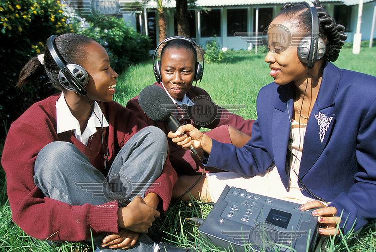 A presenter from a local radio station interviewing school girls for a youth radio programme.