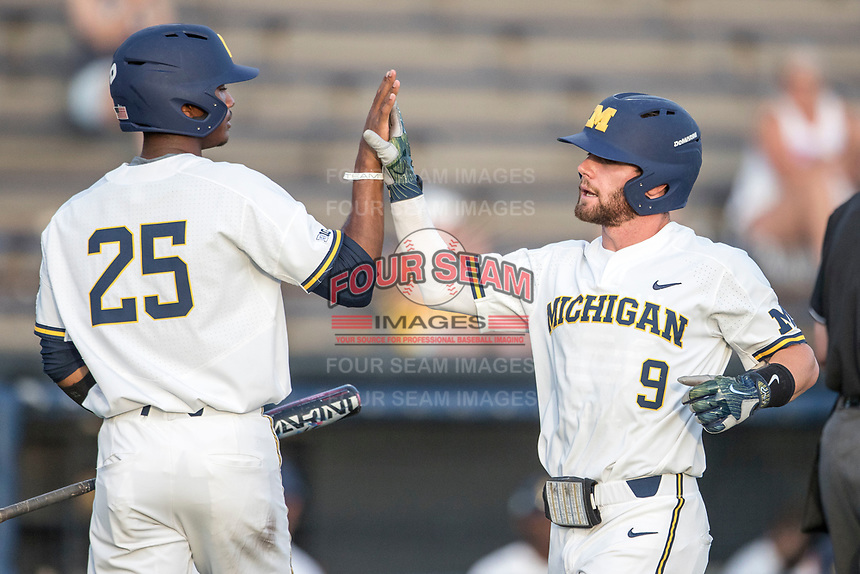 Michigan Wolverines shortstop Michael Brdar (9) is greeted at the plate by teammate Johnny Slater (25) during the NCAA baseball game against the Eastern Michigan Eagles on May 16, 2017 at Ray Fisher Stadium in Ann Arbor, Michigan. Michigan defeated Eastern Michigan 12-4. (Andrew Woolley/Four Seam Images)