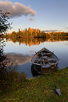 A drift boat sits in Sport Lake near Soldotna, Alaska, resting serenely in the water on a clear fall day.