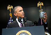 United States President Barack Obama holds up a jar of paper chips as he joking talks about meeting with Director of National Intelligence James Clapper as he speaks at a ceremony marking the 10th anniversary of the formation for the Office of the Director of National Intelligence, at it's headquarters on April 24, 2015 in McLean, Virginia. <br /> Credit: Kevin Dietsch / Pool via CNP