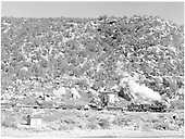 D&amp;RGW #495 passing Bondad water tank with pipe train on Farmington Branch.<br /> D&amp;RGW  Bondad, CO  Taken by Richardson, Robert W. - 2/1953