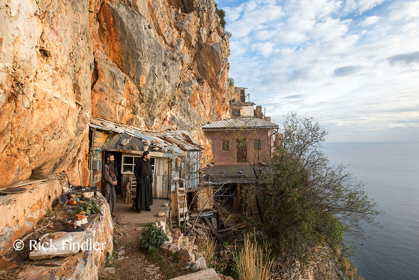 Mount Athos - The Holy Mountain.<br /> Monks look out from their cell which clings to the cliffs of Karoulia. <br /> <br /> Photographer: Rick Findler