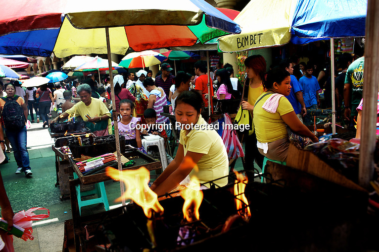 Vendors sell candles for blessings outside the Quiapo Church, also known as Minor Basilica of the Black Nazarene in Quiapo, Manila, in the Philippines. The ritual of burning or melting colored candles is believed to be offerings in exchange for heaven's blessings or divine intervention for someone's desires. Photo: Sanjit Das