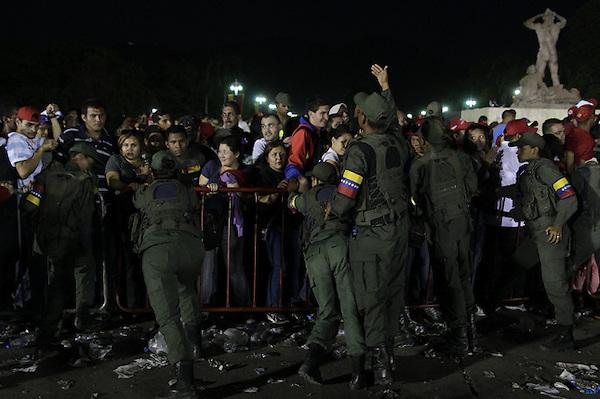 CAR255. CARACAS (VENEZUELA), 07/03/2013.- Autoridades controlan las vallas que contienen a miles de simpatizantes del presidente de Venezuela, Hugo Chávez, quienes hacen fila en los alrededores de la Academia Militar para despedir al líder fallecido hoy, jueves 7 de marzo de 2013, en Caracas, donde las hileras de gente se han mantenido a lo largo de toda la noche y desfilan ininterrumpidamente ante el féretro. EFE/David Fernández..